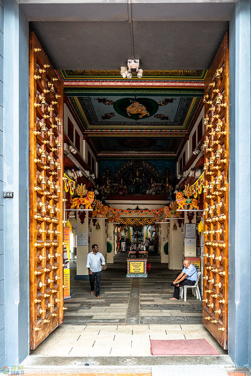 Bells in inset panels on wooden door at Mariamman temple