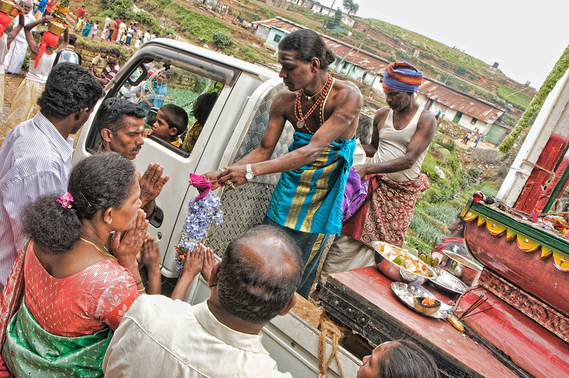 A 'holy man' takes offerings from families.