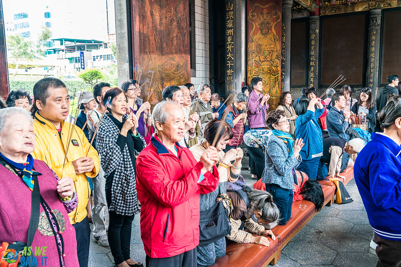 Worshippers holding joss sticks and praying in Longshan Temple