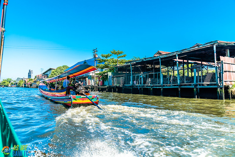 Tour boat on a Bangkok canal, leaving motorboat wake behind it.