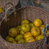 A basket of local oranges for sale in a market in Vietnam