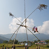 Children enjoying a bamboo swing erected for Dasain Festival, Pokhara, Nepal