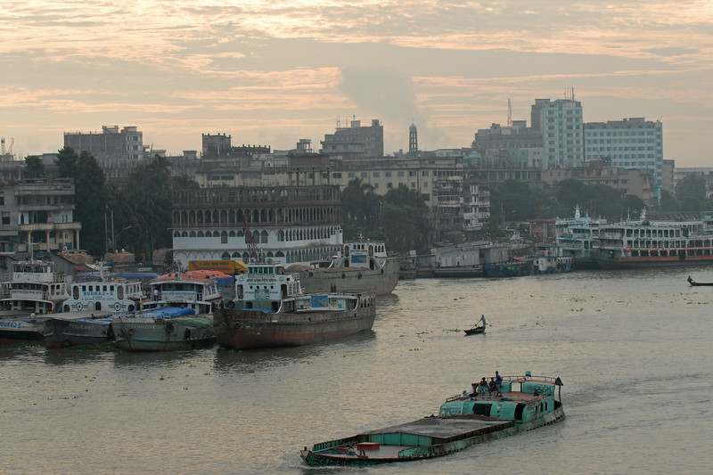 "Small boats criss cross the river all day and serve as a cheap transportation for crossing from one river bank to the other.<br /> Early morning sunrise over Buriganga River (Bangla: বুড়িগঙ্গা Buŗigônga ""Old Ganges""). Buriganga is the life line and much happens in and around this river. It is the main river flowing beside Dhaka, capital cityof Bangladesh. With an average depth of 39 feet (12 m) its quite amazing to see the activities along the river. Unfortunately, the river is Dhaka's main outlet of sewage waste and is threatened by pollution and waste. What was mind boggling was that people were using this mucky water to drink, gargle, brush their teeth and take bath all within feets of each other! Amazing immunity system!<br /> Dhaka, Bangaladesh"