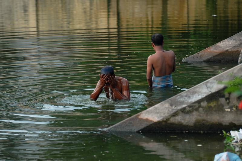 Garbage floats in the water while people are brushing, washing, bathing - all in a pool of water which appeared to be the Temple pond.<br /> Dhaka (Bangla: ঢাকা, pronounced [ɖʱaka])— (Dacca) is the capital city of Bangladesh (Bengali: বাংলাদেশ [ˈbaŋlad̪eʃ] Bangladesh). Dhaka, located on the banks of the Buriganga River is a megacity with a population of over 12 million. Dhaka is known as the City of Mosques and renowned for producing the world's finest muslin. it is a center for culture, education and business.