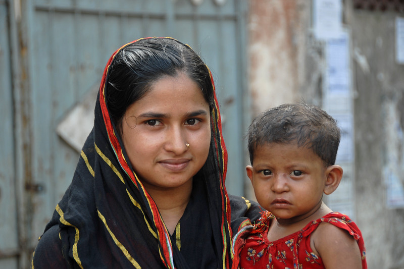 Bangladeshi mother and child pose for a picture on the street.<br /> Dhaka (Bangla: ঢাকা, pronounced [ɖʱaka])— (Dacca) is the capital city of Bangladesh (Bengali: বাংলাদেশ [ˈbaŋlad̪eʃ] Bangladesh). Dhaka, located on the banks of the Buriganga River is a megacity with a population of over 12 million. Known as the City of Mosques and renowned for producing the world's finest muslin, it is a center for culture, education and business.