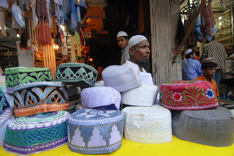 Various caps on display and sale. Iftar Delicacies of Dhaka.<br /> The holy month of Ramazan in the Muslim world is observed with great piety and fervour. The daylong fasting ends at sunset and the faithful break their fasting with the delicacies of IFTARI. <br /> Dhaka , particularly its densely populated older section bustles and buzzes with the rush home and the selling and buying of Iftari items as the time for Iftar draws near. Almost every restaurant of the city, from the 5-star hotels to local street outlets prepares their traditional and special Iftari items. Iftari items displayed on open-air stalls and tables with the adjacent gas burner or the stove frying Iftar items on large pans, some other in syrupy liquid and sizzling the other Iftaris over red-hot charcoal fire becomes the iconic Ramazan image of Dhaka.Chawk Bazar in old Dhaka is famous. The entire road in front of Shahi Masjid throbs with the hustle bustle. Jam packed with crowds.<br /> Top item is `Muri' (sand fried rice), and there is Piazu (paste of mashed lentils), `Beguni' or `Beson' (crushed yellow peas), `Jilapi' (sweetmeat), `Halim' (pasty broth), `Swami' and `Nargisi' Kabab with boiled egg, `Shik Kabab' (meats on skewers) as well as `dahi bara' (curd items). Dhaka, Bangaladesh