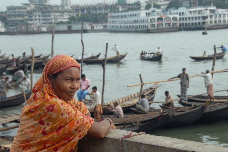 "Lady waiting for a family member at the river crossing point with the river boats in the back. Dhaka, Bangaladesh<br /> <br /> Buriganga River (Bangla: বুড়িগঙ্গা Buŗigônga ""Old Ganges""). Buriganga is the life line and much happens in and around this river. It is the main river flowing beside Dhaka, capital cityof Bangladesh. With an average depth of 39 feet (12 m) its quite amazing to see the activities along the river. Unfortunately, the river is Dhaka's main outlet of sewage waste and is threatened by pollution and waste."
