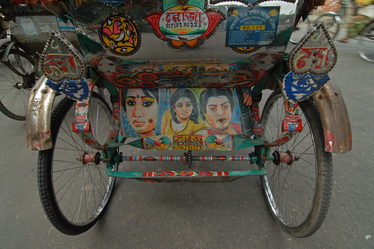 Colourful back side of a cycle rickshaw.<br /> Dhaka (Bangla: ঢাকা, pronounced [ɖʱaka])— (Dacca) is the capital city of Bangladesh (Bengali: বাংলাদেশ [ˈbaŋlad̪eʃ] Bangladesh). Dhaka, located on the banks of the Buriganga River is a megacity with a population of over 12 million. Dhaka is known as the City of Mosques and renowned for producing the world's finest muslin. it is a center for culture, education and business.