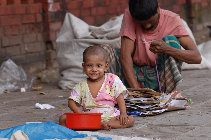 Young child on the streets of Dhaka.<br /> Dhaka (Bangla: ঢাকা, pronounced [ɖʱaka])— (Dacca) is the capital city of Bangladesh (Bengali: বাংলাদেশ [ˈbaŋlad̪eʃ] Bangladesh). Dhaka, located on the banks of the Buriganga River is a megacity with a population of over 12 million. Dhaka is known as the City of Mosques and renowned for producing the world's finest muslin. it is a center for culture, education and business.