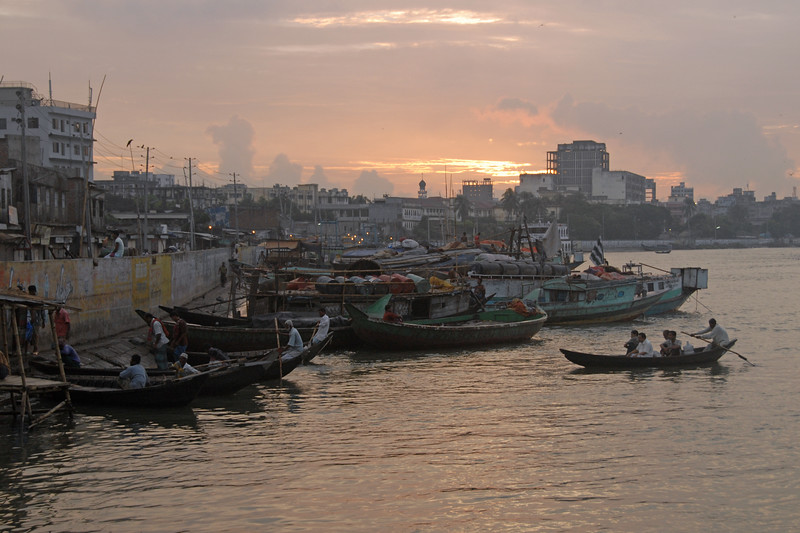 "Early morning sunrise over Buriganga River (Bangla: বুড়িগঙ্গা Buŗigônga ""Old Ganges""). Buriganga is the life line and much happens in and around this river. It is the main river flowing beside Dhaka, capital cityof Bangladesh. With an average depth of 39 feet (12 m) its quite amazing to see the activities along the river. Unfortunately, the river is Dhaka's main outlet of sewage waste and is threatened by pollution and waste. What was mind boggling was that people were using this mucky water to drink, gargle, brush their teeth and take bath all within feets of each other! Amazing immunity system!<br /> Dhaka, Bangaladesh"