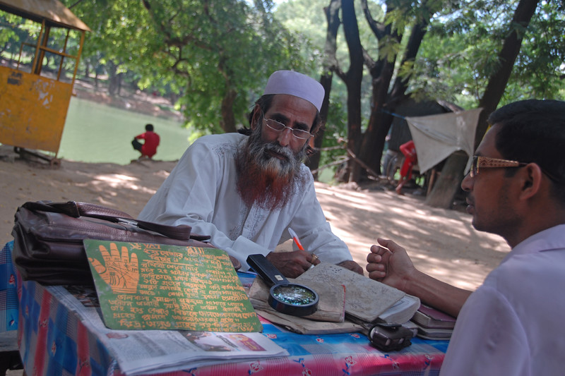 Palmist sitting in the shade in Dhaka, Bangaladesh with a customer in front.