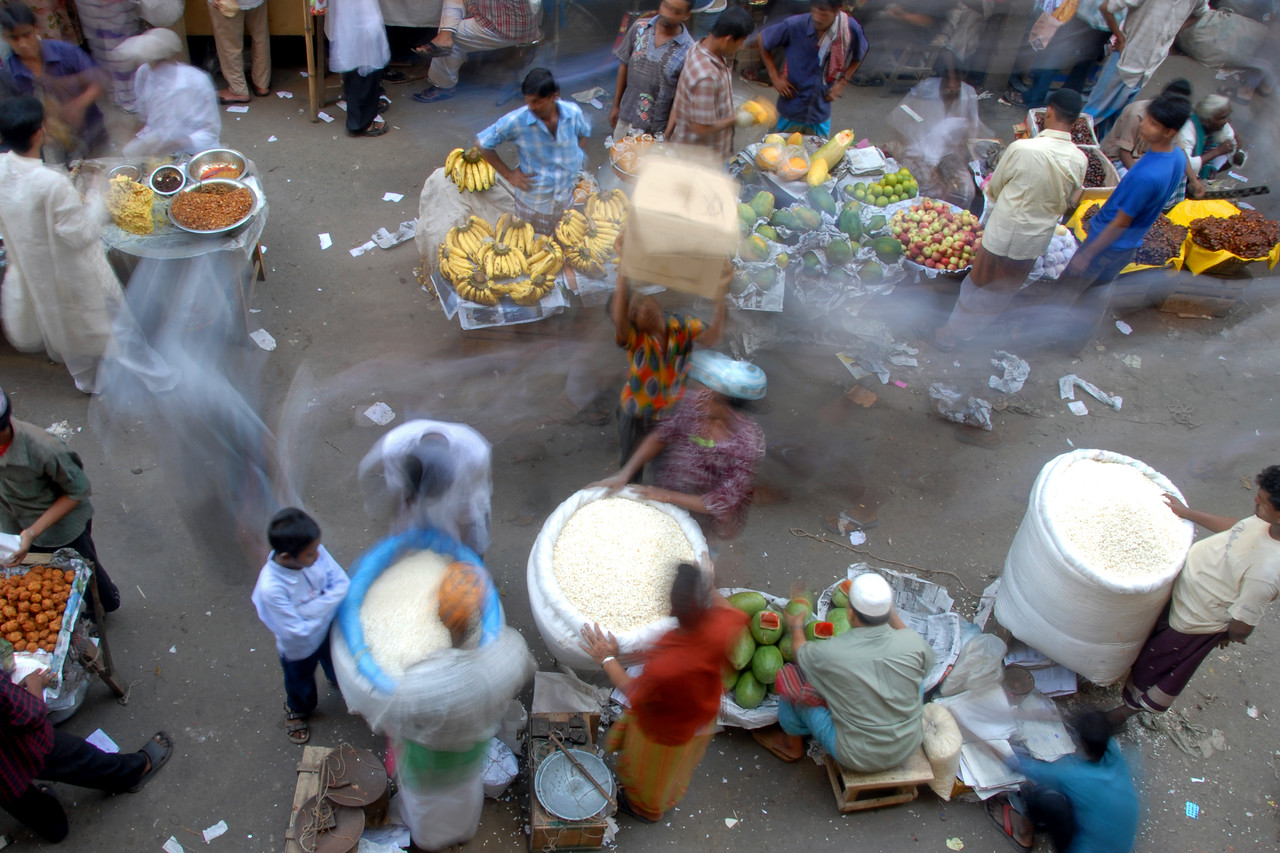 Hand held image - motion blur of people moving around in the bazaar. <br /> Iftar Delicacies of Dhaka. The holy month of Ramazan in the Muslim world is observed with great piety and fervour. The daylong fasting ends at sunset and the faithful break their fasting with the delicacies of IFTARI. <br /> Dhaka , particularly its densely populated older section bustles and buzzes with the rush home and the selling and buying of Iftari items as the time for Iftar draws near. Almost every restaurant of the city, from the 5-star hotels to local street outlets prepares their traditional and special Iftari items. Iftari items displayed on open-air stalls and tables with the adjacent gas burner or the stove frying Iftar items on large pans, some other in syrupy liquid and sizzling the other Iftaris over red-hot charcoal fire becomes the iconic Ramazan image of Dhaka.Chawk Bazar in old Dhaka is famous. The entire road in front of Shahi Masjid throbs with the hustle bustle. Jam packed with crowds.<br /> Top item is `Muri' (sand fried rice), and there is Piazu (paste of mashed lentils), `Beguni' or `Beson' (crushed yellow peas), `Jilapi' (sweetmeat), `Halim' (pasty broth), `Swami' and `Nargisi' Kabab with boiled egg, `Shik Kabab' (meats on skewers) as well as `dahi bara' (curd items). Dhaka, Bangaladesh