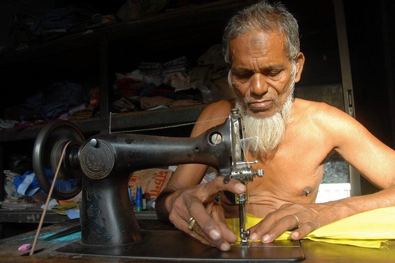 As the wheels turn. A doorji (darji - tailor) sitting in the side lane stitching cloths.<br /> Dhaka (Bangla: ঢাকা, pronounced [ɖʱaka])— (Dacca) is the capital city of Bangladesh (Bengali: বাংলাদেশ [ˈbaŋlad̪eʃ] Bangladesh). Dhaka, located on the banks of the Buriganga River is a megacity with a population of over 12 million. Dhaka is known as the City of Mosques and renowned for producing the world's finest muslin. it is a center for culture, education and business.