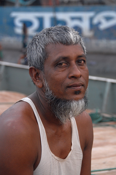 "Portrait of one of the men on the boat/barge.<br /> Early morning sunrise over Buriganga River (Bangla: বুড়িগঙ্গা Buŗigônga ""Old Ganges""). Buriganga is the life line and much happens in and around this river. It is the main river flowing beside Dhaka, capital cityof Bangladesh. With an average depth of 39 feet (12 m) its quite amazing to see the activities along the river. Unfortunately, the river is Dhaka's main outlet of sewage waste and is threatened by pollution and waste. What was mind boggling was that people were using this mucky water to drink, gargle, brush their teeth and take bath all within feets of each other! Amazing immunity system!<br /> Dhaka, Bangaladesh"