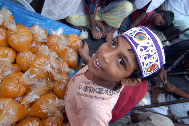 Happy young boy goes about selling his wares. Iftar Delicacies being sold in the streets of Old Dhaka.<br /> The holy month of Ramazan in the Muslim world is observed with great piety and fervour. The daylong fasting ends at sunset and the faithful break their fasting with the delicacies of IFTARI. <br /> Dhaka , particularly its densely populated older section bustles and buzzes with the rush home and the selling and buying of Iftari items as the time for Iftar draws near. Almost every restaurant of the city, from the 5-star hotels to local street outlets prepares their traditional and special Iftari items. Iftari items displayed on open-air stalls and tables with the adjacent gas burner or the stove frying Iftar items on large pans, some other in syrupy liquid and sizzling the other Iftaris over red-hot charcoal fire becomes the iconic Ramazan image of Dhaka.Chawk Bazar in old Dhaka is famous. The entire road in front of Shahi Masjid throbs with the hustle bustle. Jam packed with crowds.<br /> Top item is `Muri' (sand fried rice), and there is Piazu (paste of mashed lentils), `Beguni' or `Beson' (crushed yellow peas), `Jilapi' (sweetmeat), `Halim' (pasty broth), `Swami' and `Nargisi' Kabab with boiled egg, `Shik Kabab' (meats on skewers) as well as `dahi bara' (curd items). Dhaka, Bangaladesh