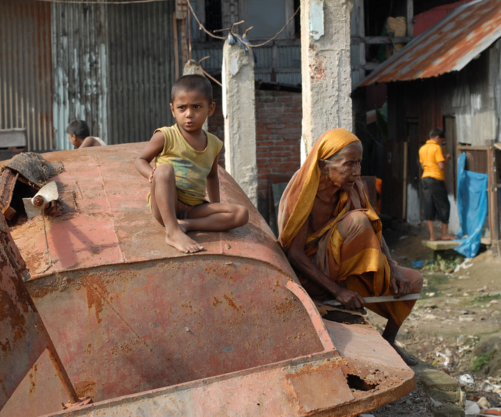 "Children in various states of dress and undress (near nakedness) playing in the water and on the banks. Old lady taking a rest while a little child sits on top of a majorly rusted boat. Dhaka, Bangaladesh<br /> <br /> Buriganga River (Bangla: বুড়িগঙ্গা Buŗigônga ""Old Ganges""). Buriganga is the life line and much happens in and around this river. It is the main river flowing beside Dhaka, capital cityof Bangladesh. With an average depth of 39 feet (12 m) its quite amazing to see the activities along the river. Unfortunately, the river is Dhaka's main outlet of sewage waste and is threatened by pollution and waste."