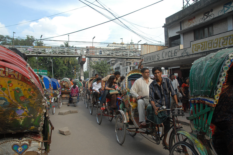 There are a huge number of cycle-rickshaws in the city. Bumper to bumper at times.<br /> <br /> Dhaka (Bangla: ঢাকা, pronounced [ɖʱaka])— (Dacca) is the capital city of Bangladesh (Bengali: বাংলাদেশ [ˈbaŋlad̪eʃ] Bangladesh). Dhaka, located on the banks of the Buriganga River is a megacity with a population of over 12 million. Dhaka, located on the banks of the Buriganga River is a megacity with a population of over 12 million. Known as the City of Mosques and renowned for producing the world's finest muslin, it is a center for culture, education and business.