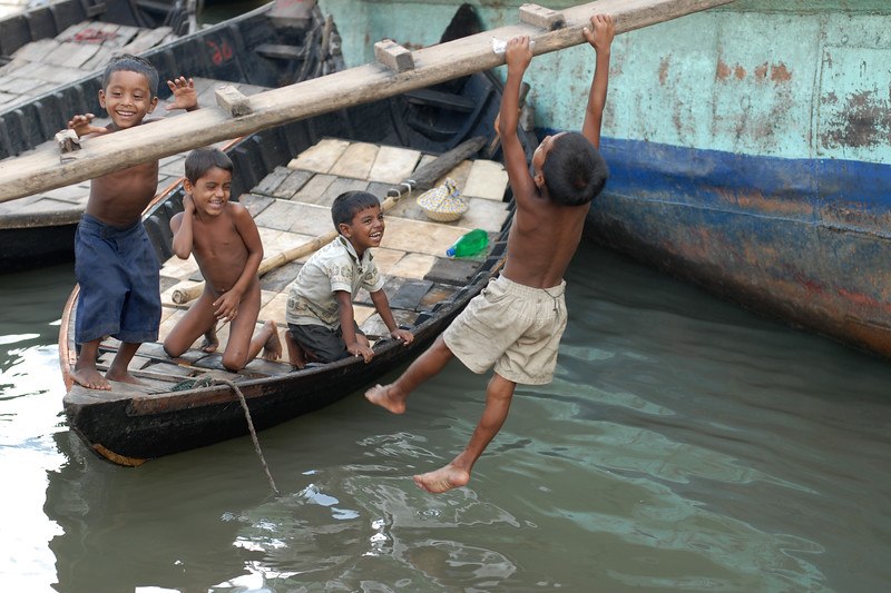 "Children in various states of dress and undress (near nakedness) playing in the water and swinging & monkeying around. Some having bath, others just having fun. But what is amazing is their immunity system and ability to handle the conditions. Since this is the river banks of Buriganga - one of the most polluted rivers. Within inches and feets of them are leaking oil drums, welding sharpels, garbage, waste plasitc, and God knows what else! Yet in this very same water of the river children can be seen swiming, playing, drinking water without aparent problems or infection. The same water has the ship breaking activities with oil leaking, tar burning, and more making the river thick black. Dhaka, Bangaladesh<br /> <br /> Buriganga River (Bangla: বুড়িগঙ্গা Buŗigônga ""Old Ganges""). Buriganga is the life line and much happens in and around this river. It is the main river flowing beside Dhaka, capital cityof Bangladesh. With an average depth of 39 feet (12 m) its quite amazing to see the activities along the river. Unfortunately, the river is Dhaka's main outlet of sewage waste and is threatened by pollution and waste."