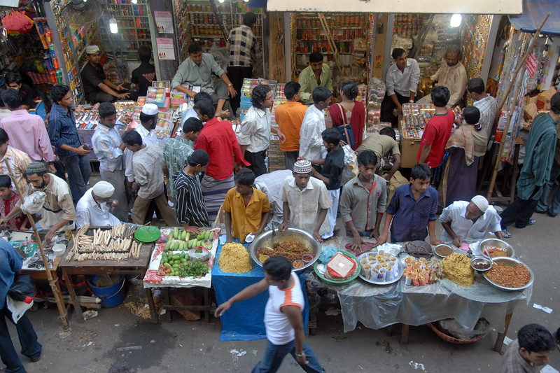 Packed streets of old Dhaka with Iftar delicacies being sold.<br /> The holy month of Ramazan in the Muslim world is observed with great piety and fervour. The daylong fasting ends at sunset and the faithful break their fasting with the delicacies of IFTARI. <br /> Dhaka , particularly its densely populated older section bustles and buzzes with the rush home and the selling and buying of Iftari items as the time for Iftar draws near. Almost every restaurant of the city, from the 5-star hotels to local street outlets prepares their traditional and special Iftari items. Iftari items displayed on open-air stalls and tables with the adjacent gas burner or the stove frying Iftar items on large pans, some other in syrupy liquid and sizzling the other Iftaris over red-hot charcoal fire becomes the iconic Ramazan image of Dhaka.Chawk Bazar in old Dhaka is famous. The entire road in front of Shahi Masjid throbs with the hustle bustle. Jam packed with crowds.<br /> Top item is `Muri' (sand fried rice), and there is Piazu (paste of mashed lentils), `Beguni' or `Beson' (crushed yellow peas), `Jilapi' (sweetmeat), `Halim' (pasty broth), `Swami' and `Nargisi' Kabab with boiled egg, `Shik Kabab' (meats on skewers) as well as `dahi bara' (curd items). Dhaka, Bangaladesh