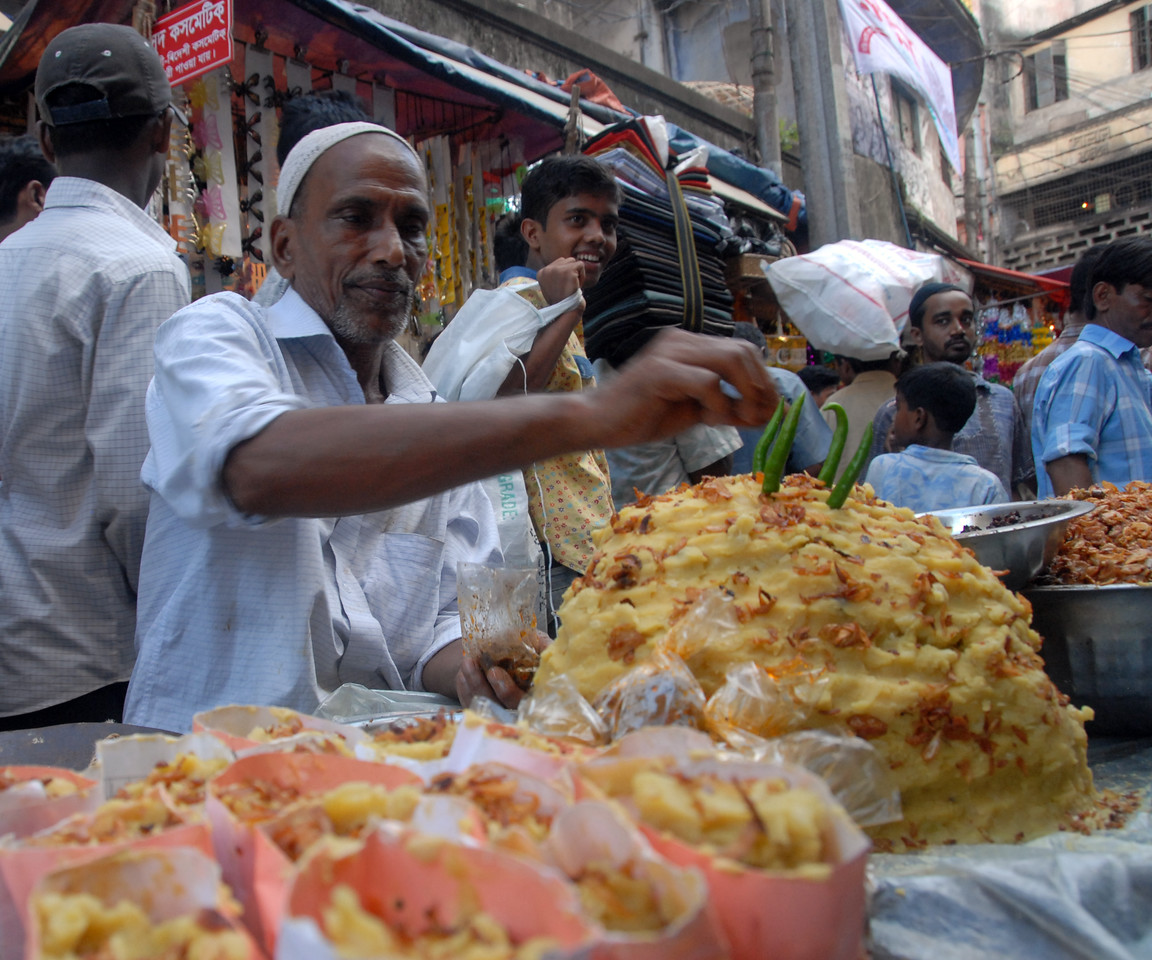 Brisk sales of Iftar delicacies in Dhaka.<br /> The holy month of Ramazan in the Muslim world is observed with great piety and fervour. The daylong fasting ends at sunset and the faithful break their fasting with the delicacies of IFTARI. <br /> Dhaka , particularly its densely populated older section bustles and buzzes with the rush home and the selling and buying of Iftari items as the time for Iftar draws near. Almost every restaurant of the city, from the 5-star hotels to local street outlets prepares their traditional and special Iftari items. Iftari items displayed on open-air stalls and tables with the adjacent gas burner or the stove frying Iftar items on large pans, some other in syrupy liquid and sizzling the other Iftaris over red-hot charcoal fire becomes the iconic Ramazan image of Dhaka.Chawk Bazar in old Dhaka is famous. The entire road in front of Shahi Masjid throbs with the hustle bustle. Jam packed with crowds.<br /> Top item is `Muri' (sand fried rice), and there is Piazu (paste of mashed lentils), `Beguni' or `Beson' (crushed yellow peas), `Jilapi' (sweetmeat), `Halim' (pasty broth), `Swami' and `Nargisi' Kabab with boiled egg, `Shik Kabab' (meats on skewers) as well as `dahi bara' (curd items). Dhaka, Bangaladesh