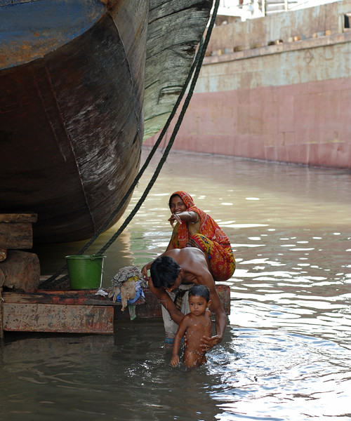 "Lady doing her laundry while the father giving a bath to children in various states of dress and undress (near nakedness) while they playing in the water. Some having bath, others just having fun. But what is amazing is their immunity system and ability to handle the conditions. Since this is the river banks of Buriganga - one of the most polluted rivers. Within inches and feets of them are leaking oil drums, welding sharpels, garbage, waste plasitc, and God knows what else! Yet in this very same water of the river children can be seen swiming, playing, drinking water without aparent problems or infection. The same water has the ship breaking activities with oil leaking, tar burning, and more making the river thick black. Dhaka, Bangaladesh<br /> <br /> Buriganga River (Bangla: বুড়িগঙ্গা Buŗigônga ""Old Ganges""). Buriganga is the life line and much happens in and around this river. It is the main river flowing beside Dhaka, capital cityof Bangladesh. With an average depth of 39 feet (12 m) its quite amazing to see the activities along the river. Unfortunately, the river is Dhaka's main outlet of sewage waste and is threatened by pollution and waste."