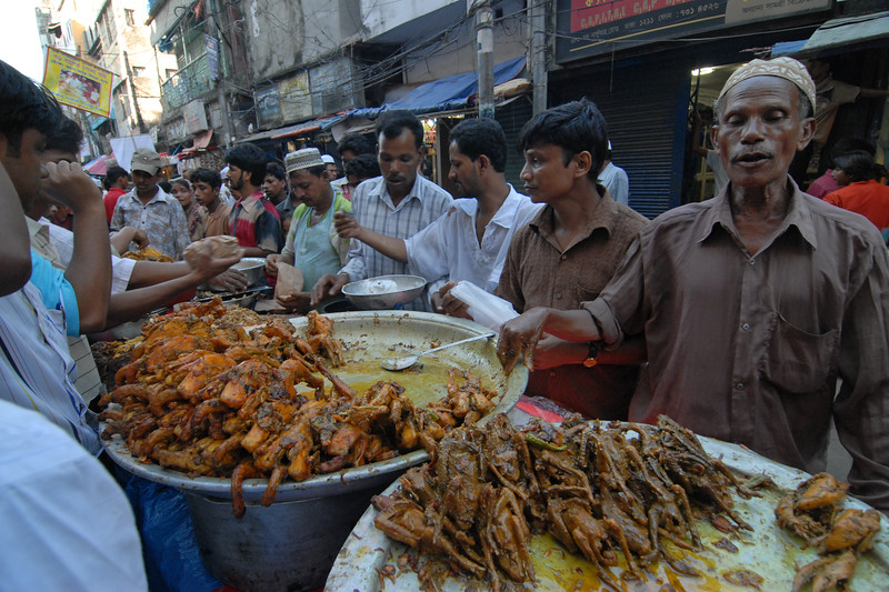 Iftar Delicacies of Dhaka.<br /> The holy month of Ramazan in the Muslim world is observed with great piety and fervour. The daylong fasting ends at sunset and the faithful break their fasting with the delicacies of IFTARI. <br /> Dhaka , particularly its densely populated older section bustles and buzzes with the rush home and the selling and buying of Iftari items as the time for Iftar draws near. Almost every restaurant of the city, from the 5-star hotels to local street outlets prepares their traditional and special Iftari items. Iftari items displayed on open-air stalls and tables with the adjacent gas burner or the stove frying Iftar items on large pans, some other in syrupy liquid and sizzling the other Iftaris over red-hot charcoal fire becomes the iconic Ramazan image of Dhaka.Chawk Bazar in old Dhaka is famous. The entire road in front of Shahi Masjid throbs with the hustle bustle. Jam packed with crowds.<br /> Top item is `Muri' (sand fried rice), and there is Piazu (paste of mashed lentils), `Beguni' or `Beson' (crushed yellow peas), `Jilapi' (sweetmeat), `Halim' (pasty broth), `Swami' and `Nargisi' Kabab with boiled egg, `Shik Kabab' (meats on skewers) as well as `dahi bara' (curd items). Dhaka, Bangaladesh