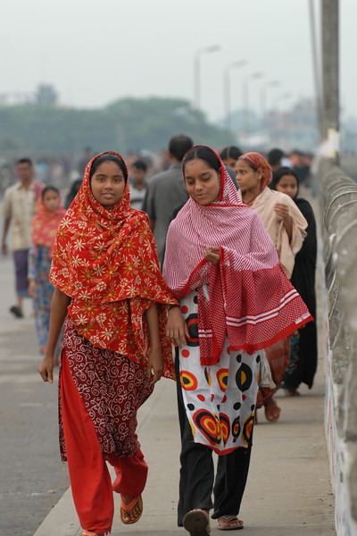 "Men and women going about their daily chores. Seen here they are crossing one of the main bridges  - Buriganga Bridge No. 2. - over  Buriganga River (Bangla: বুড়িগঙ্গা Buŗigônga ""Old Ganges""). Buriganga is the life line and much happens in and around this river. It is the main river flowing beside Dhaka, capital cityof Bangladesh. Dhaka, Bangaladesh"