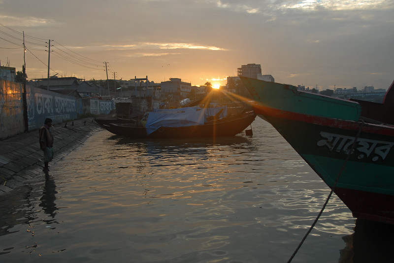 """Early morning sunrise over Buriganga River (Bangla: বুড়িগঙ্গা Buŗigônga """"Old Ganges"""") as the man on the left brushes his teeth. <br /> <br /> Buriganga is the life line and much happens in and around this river. It is the main river flowing beside Dhaka, capital cityof Bangladesh. With an average depth of 39 feet (12 m) its quite amazing to see the activities along the river. Unfortunately, the river is Dhaka's main outlet of sewage waste and is threatened by pollution and waste. What was mind boggling was that people were using this mucky water to drink, gargle, brush their teeth and take bath all within feets of each other! Amazing immunity system!<br /> Dhaka, Bangaladesh"""