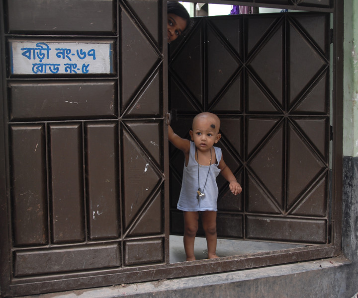 """Small child peeping out of the home in the back lanes near Buriganga, Dhaka, Bangaladesh<br /> <br /> Buriganga River (Bangla: বুড়িগঙ্গা Buŗigônga """"Old Ganges""""). Buriganga is the life line and much happens in and around this river. It is the main river flowing beside Dhaka, capital cityof Bangladesh. With an average depth of 39 feet (12 m) its quite amazing to see the activities along the river. Unfortunately, the river is Dhaka's main outlet of sewage waste and is threatened by pollution and waste."""