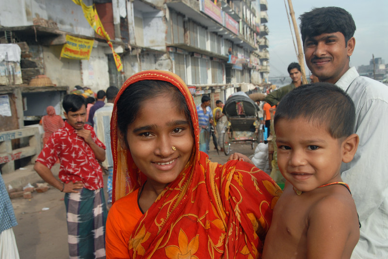 Bangladeshi mother with her child. With some coaxing the boy had a smile on his face. Dhaka, Bangaladesh