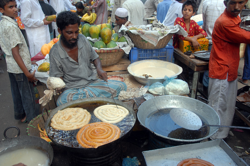 Huge sized hot jalebis. Iftar Delicacies of Dhaka.<br /> The holy month of Ramazan in the Muslim world is observed with great piety and fervour. The daylong fasting ends at sunset and the faithful break their fasting with the delicacies of IFTARI. The fasting is meant to teach a person patience, humility and sacrifice, to set aside time to ask forgiveness, practice self-restraint, and pray for guidance in the future. Dhaka , particularly its densely populated older section bustles and buzzes with the rush home and the selling and buying of Iftari items as the time for Iftar draws near. Almost every restaurant of the city, from the 5-star hotels to local street outlets prepares their traditional and special Iftari items. Iftari items displayed on open-air stalls and tables with the adjacent gas burner or the stove frying Iftar items on large pans, some other in syrupy liquid and sizzling the other Iftaris over red-hot charcoal fire becomes the iconic Ramazan image of Dhaka.Chawk Bazar in old Dhaka is famous. The entire road in front of Shahi Masjid throbs with the hustle bustle. Jam packed with crowds.<br /> Top item is `Muri' (sand fried rice), and there is Piazu (paste of mashed lentils), `Beguni' or `Beson' (crushed yellow peas), `Jilapi' (sweetmeat), `Halim' (pasty broth), `Swami' and `Nargisi' Kabab with boiled egg, `Shik Kabab' (meats on skewers) as well as `dahi bara' (curd items). Dhaka, Bangaladesh
