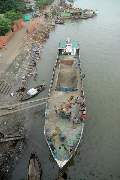 """Sand digging, shipping and transport is a big business. Seen here on the  river bank of Buriganga River (Bangla: বুড়িগঙ্গা Buŗigônga """"Old Ganges""""). Buriganga is the life line and much happens in and around this river. It is the main river flowing beside Dhaka, capital cityof Bangladesh. With an average depth of 39 feet (12 m) its quite amazing to see the activities along the river. Unfortunately, the river is Dhaka's main outlet of sewage waste and is threatened by pollution and waste. Dhaka, Bangaladesh"""