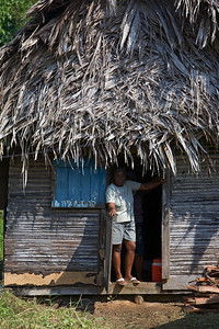 Woman standing at her door in old wooden thatch house, Barranco Village, Toledo, Belize.