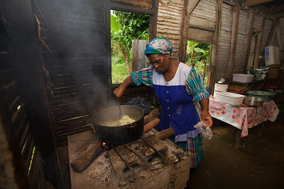 Women cooking darasa and rice and beans on open fire hearth in a small thatched kitchen in Barranco Village, Toledo, Belize.