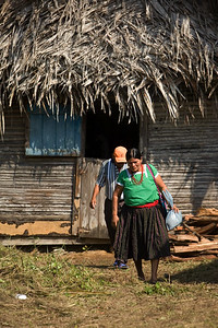 Mayan couple leaving old wooden thatch home in Barranco Village, Toledo.