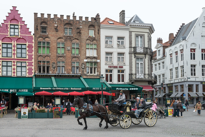 Traditional horse carriages at Place De Bruges. The Markt of Bruges is located in the heart of the city and covers an area of about 1 hectare. Some historical highlights around the square include the 12th-century belfry and the Provincial Court.