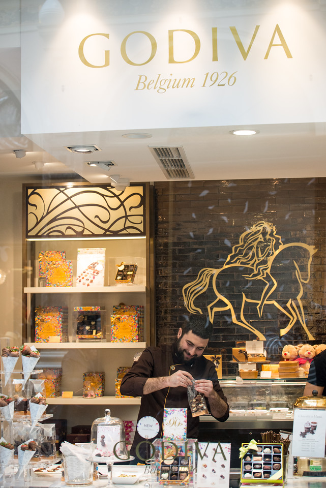 Godiva Belgian chocolate store at Koninklijke Sint-Hubertusgalerijen. The Galeries Royales Saint-Hubert (French) or Koninklijke Sint-Hubertusgalerijen (Dutch) is a glazed shopping arcade in Brussels that preceded other famous 19th-century shopping arcades such as the Galleria Vittorio Emanuele II in Milan and The Passage in St Petersburg. Like them it has twin regular façades with distant origins in Vasari's long narrow street-like courtyard of the Uffizi, Florence, with glazed arcaded shopfronts separated by pilasters and two upper floors, all in an Italianate Cinquecento style, under an arched glass-paned roof with a delicate cast-iron framework.