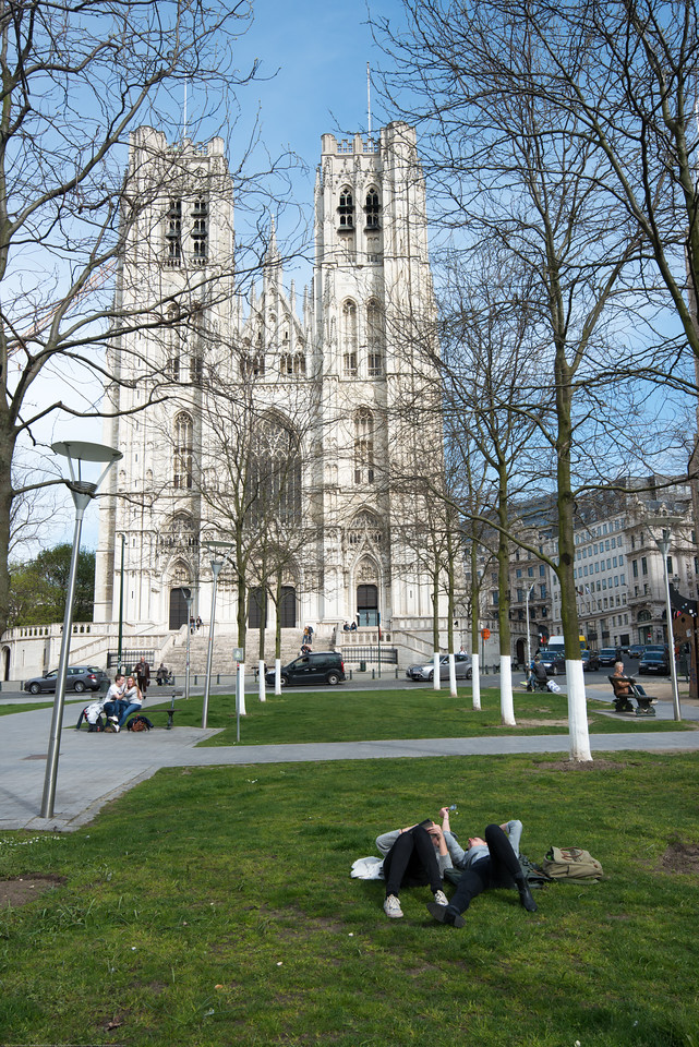 People relax on the grass and benches at St Michael and St Gudula Cathedral, Brussels, Place Sainte-Gudule, Brussels, Belgium.