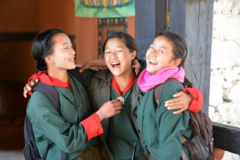 Smiling, laughing, beautiful young girl students on a bridge right outside Paro Rinpung Dzong. Rinpung Dzong is a large dzong - Buddhist monastery and fortress - of the Drukpa Lineage of the Kagyu school in Paro District in Bhutan.