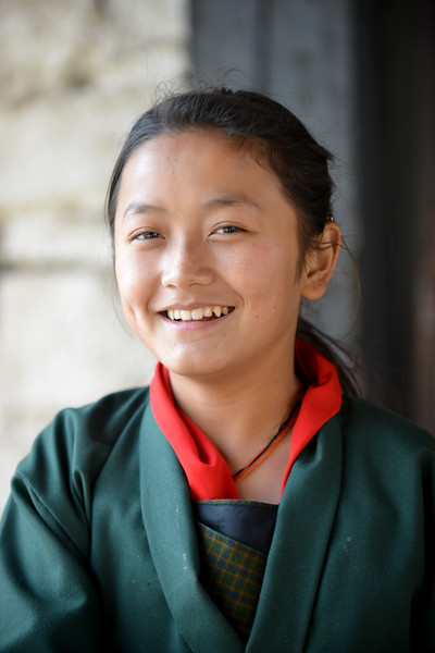 Smiling beautiful young girl students on a bridge right outside Paro Rinpung Dzong. Rinpung Dzong is a large dzong - Buddhist monastery and fortress - of the Drukpa Lineage of the Kagyu school in Paro District in Bhutan.