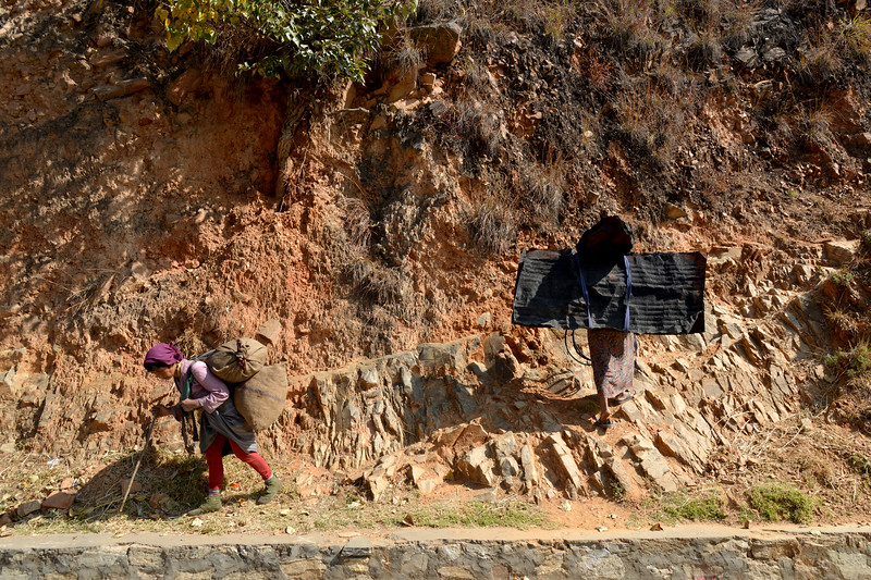 Old ladies carrying heavy loads on the roads of Paro, Bhutan.