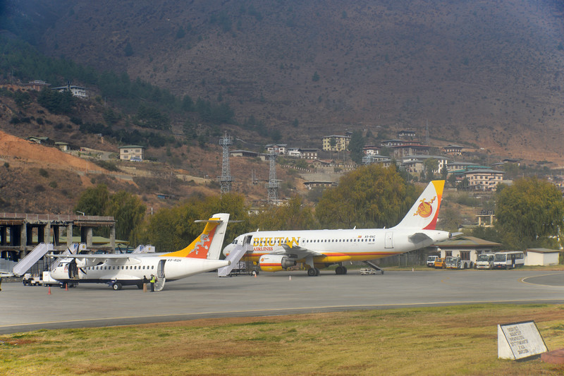 DrukAir planes at the Paro International Airport in Bhutan. <br /> <br /> In 1968, the Indian Border Roads Organisation built an airstrip in the Paro valley, which was initially utilised for on call helicopter operations by the Indian Armed Forces for the Royal Government of Bhutan. After consideration by King Jigme Singye Wangchuck and the Tshogdu, Drukair was established by Royal Charter on 5 April 1981, ten years after the Druk Gyalpo, King Jigme Dorji Wangchuck gradually began to open up the Kingdom from self-imposed isolation, and seven years after welcoming its first foreign visitors.  India helped build the Paro Airport <br /> and now the Government of India (GoI) has committed Nu 680M, in principle, for the expansion of Paro international airport in the 11th five-year plan (FYP).