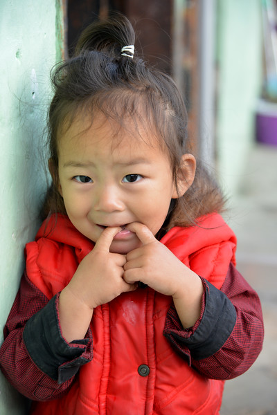 Little girl outside her mother's shop on the streets of Paro, Bhutan.