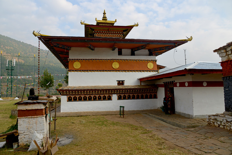 "The Temple of Fertility (Chimi L'hakhang Temple), Punakha, Bhutan. The site was blessed by the ""Divine Madman"" the maverick saint Drukpa Kunley (1455–1529) who built a chorten on the site. The Lhakhang is of modest size, square in shape with a golden spire. It is a golden yellow roofed building. It has a row of prayer wheels and its exterior walls are embedded with slates carved with images of saints. Near the entrance to the Lakhang, there is this small chorten which marks the location where the demoness was subdued by Lama Kunley. This small 16th century temple of fertility is dedicated to the Lama Drukpa Kunley, the 'Divine Madman', decorated with colourful phalluses and visited by childless couples seeking a special blessing to beget children. This is one of the highly revered temples in all of Bhutan."