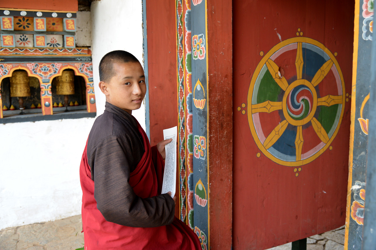 "Student monks at the Temple of Fertility (Chimi L'hakhang Temple), Punakha, Bhutan. The site was blessed by the ""Divine Madman"" the maverick saint Drukpa Kunley (1455–1529) who built a chorten on the site. In founding the site it is said that Lama Kunley subdued a demon of Dochu La with his ""magic thunderbolt of wisdom"" and trapped it in a rock at the location close to where the chorten now stands. He was known as the ""Mad Saint"" or ""Divine Madman"" for his unorthodox ways of teaching Buddhism by singing, humour and outrageous behaviour, which amounted to being bizarre, shocking and with sexual overtones. He is also the saint who advocated the use of phallus symbols as paintings on walls and as flying carved wooden phalluses on house tops at four corners of the eves. The monastery is the repository of the original wooden symbol of phallus that Kunley brought from Tibet. This wooden phallus is decorated with a silver handle and is used to bless people who visit the monastery on pilgrimage, particularly women seeking blessings to beget children. The tradition at the monastery is to strike pilgrims on the head with a 10 inch (25 cm) wooden phallus (erect penis). Traditionally symbols of an erect penis in Bhutan have been intended to drive away the evil eye and malicious gossip."