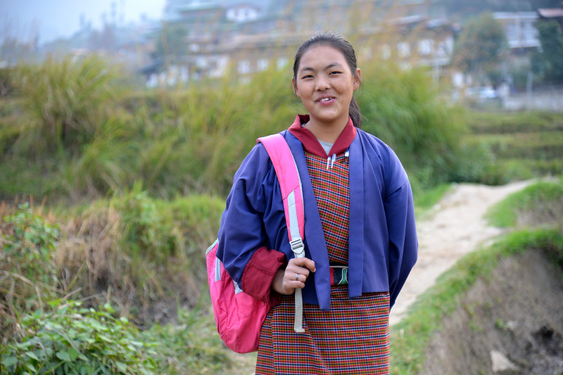 Young girl returning from school to her home in the village in Punakha, Bhutan wearing her school uniform and with her school bag.
