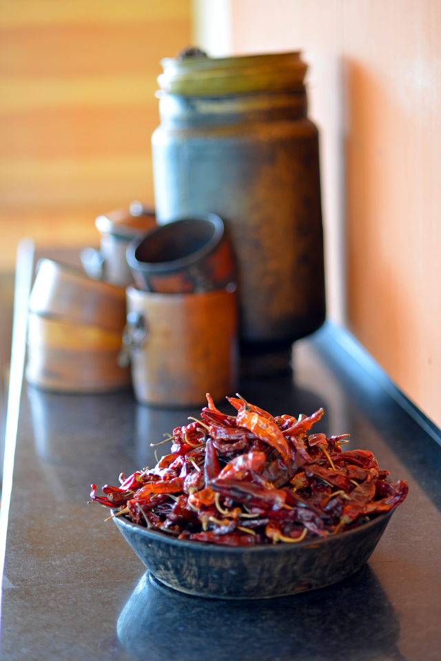 Bowl of dry hot red chillies, milk containers, and other utensils on display at the restuarant.<br /> Dhensa Boutique Resorts opened its first resort in Bhutan's Punakha Valley in March 2014. Dhensa Resort is a boutique property, located in the heart of Bhutan's verdant and lush Punakha Valley. Flanked by thick pine forests, it overlooks the Punakha River and is surrounded by several walking and trekking trails.