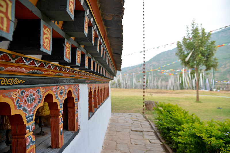 "The Temple of Fertility (Chimi L'hakhang Temple), Punakha, Bhutan. The site was blessed by the ""Divine Madman"" the maverick saint Drukpa Kunley (1455–1529) who built a chorten on the site. In founding the site it is said that Lama Kunley subdued a demon of Dochu La with his ""magic thunderbolt of wisdom"" and trapped it in a rock at the location close to where the chorten now stands. He was known as the ""Mad Saint"" or ""Divine Madman"" for his unorthodox ways of teaching Buddhism by singing, humour and outrageous behaviour, which amounted to being bizarre, shocking and with sexual overtones. He is also the saint who advocated the use of phallus symbols as paintings on walls and as flying carved wooden phalluses on house tops at four corners of the eves. The monastery is the repository of the original wooden symbol of phallus that Kunley brought from Tibet. This wooden phallus is decorated with a silver handle and is used to bless people who visit the monastery on pilgrimage, particularly women seeking blessings to beget children. The tradition at the monastery is to strike pilgrims on the head with a 10 inch (25 cm) wooden phallus (erect penis). Traditionally symbols of an erect penis in Bhutan have been intended to drive away the evil eye and malicious gossip."