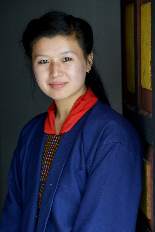 Smart young lady who is a student at the National Institute for Zorig Chusum, Dept of Human Resources, Thimphu, Bhutan strikes a pose at the entrance.<br /> <br /> Commonly known as 'the painting school', four to six-year courses provide instruction in Bhutan's 13 traditional arts and students specialise in painting (furniture, thangka – painted religious pictures, usually on canvas), woodcarving (masks, statues, bowls), embroidery (hangings, boots, clothes) or statue-making (clay).