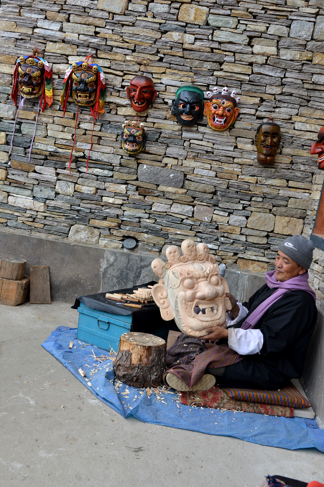 An artist sitting outside the National Library and Archives and Foreign Language Library Block of Bhutan at Thimphu, Bhutan handcrafting wooden masks.